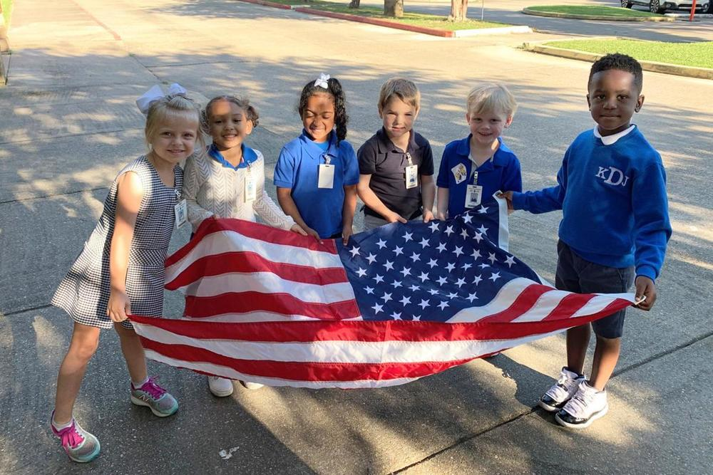 Bains Lower Elementary School students help raise the flag high