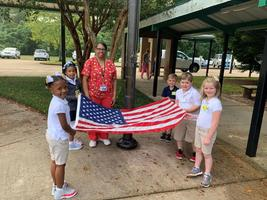 Students raise the flag as part of morning routine at Bains Lower