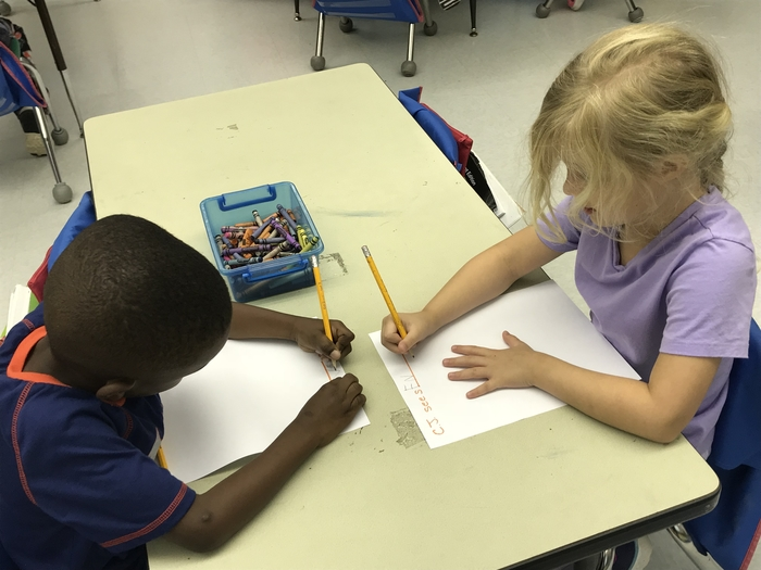Kindergarten students writing a response to a story.